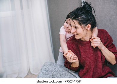 Happy Caucasian mother and her child playing together at home. Girl and mom in casual sitting on the carpet. Happy mum and kid having fun, smiling and hugging. Family holiday and togetherness.