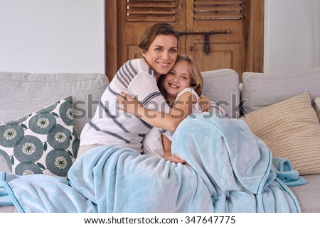 5270318804 happy caucasian mother hugging cuddling her daughter sitting on the coach  all snuggled with a blanket