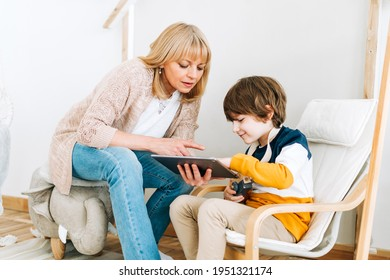 Happy caucasian mother sitting with son in children's room, looking at tablet computer device. Smiling family plays video games with kid boy together. Mom and chilld wathcing on touch screen.