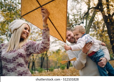 Happy Caucasian parents and his son enjoying flying toy kite in nature. Young family having fun at summer outdoor. Mother father and child walking and playing outside
