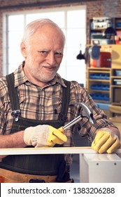 Happy caucasian pensioner hammering at DIY home workshop. Looking at camera, smiling.