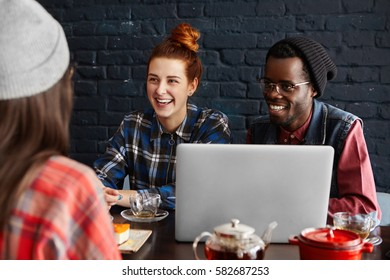 Happy Caucasian redhead girl and her dark-skinned boyfriend wearing glasses and stylish hat sitting at cafe in front of open laptop, laughing and looking at their common female friend in foreground