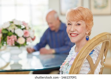 Happy caucasian Senior Couple in Dining room. Female sitting looking at camera. Senior husband out of focus looking at papers at table. Bright and Airy.