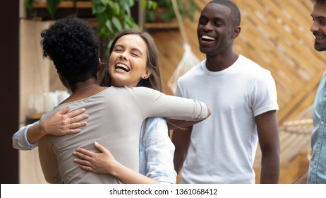Happy caucasian teen girl embracing african american friend having fun at group meeting, cheerful diverse young women laughing hugging greeting celebrating reunion multi ethnic friendship outdoors