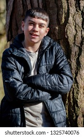 Happy caucasian teenage boy wearing a jacket leaning on a tree on a spring day