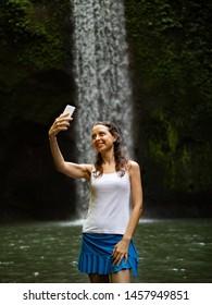 Happy Caucasian woman enjoying waterfall landscape in tropic, making selfie with smartphone near waterfall. Lifestyle travel blogger. Luxury vacation in Asia. Tibumana waterfall Ubud, Bali, Indonesia