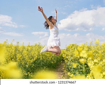 Happy caucasian woman jumping up with raised hands outdoor. Yellow flowers field around