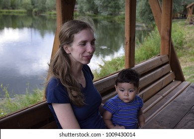 happy, caucasian, woman with latin baby resting in a gazebo on the lake in the city park
