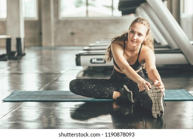 Happy Caucasian woman stretching her leg on before workout in gym