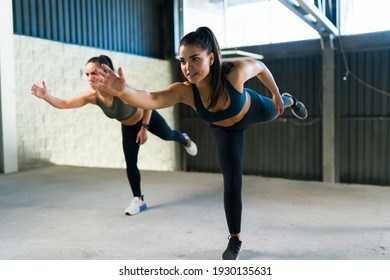 Happy caucasian women smiling and training at the gym during a HIIT class. Two active and beautiful women doing runner touches