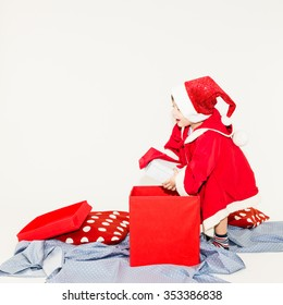 Happy caucasian Xmas toddler opening a big Christmas gift box - isolated on white background
