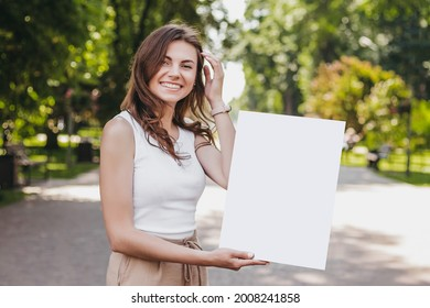 Happy caucasian young brunette woman holding a poster in her hands and smiling on the background of the park