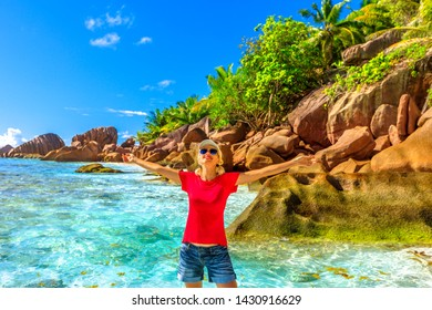 Happy caucasian young woman with open arms on turquoise waters at Anse Cocos near Grande Anse and Petite Anse in La Digue Island. Joyful tourist girl at Seychelles. Summer tropical beach. Blue sky.
