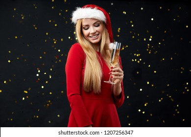 Happy celebrated woman holding shampagne glass over black sparkling background. Isolated portrait of smiling businesswoman wearing christmas hat, ready to celebrate Christmas holidays