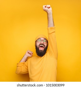 Happy celebrating bearded man in yellow hat posing with hands up.
