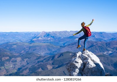 Happy celebrating winning success woman with arms raised in of having reached mountain top summit goal during hiking travel trek.