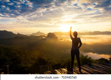 Happy celebrating winning success woman at sunrise standing  with arms raised up above her head in celebration of having reached mountain top summit goal during hiking travel trek,copy space.