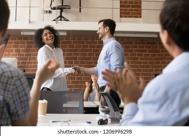 Happy ceo and team congratulating successful african american worker by shaking clapping hands, smiling black employee excited by reward bonus promotion, handshake as gratitude recognition concept