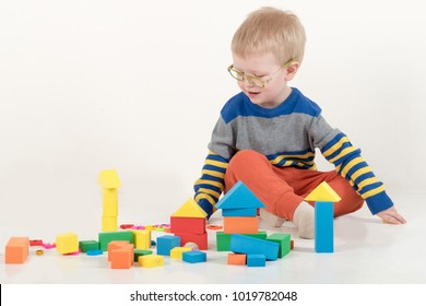 Happy charming Caucasian blond kid in colored clothes playing with plastic letters. Learning the alphabet, preparing for school. Education for kindergarten and preschool children. White background