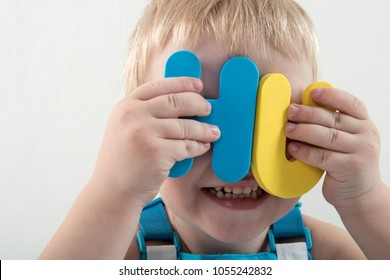 Happy charming Caucasian blond's kid in colored clothes playing with plastic letters. Learning the alphabet, preparing for school. Education for kindergarten and preschool children. White background