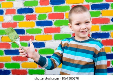 Happy charming caucasian child painting a brick wall. Brush, container with paint.