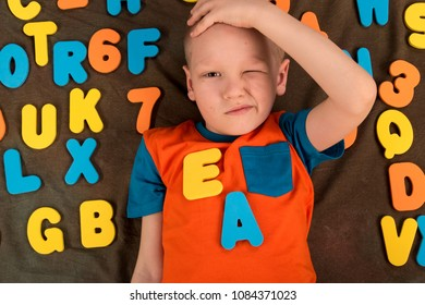 Happy charming Caucasian kid in colored clothes playing with plastic letters. Learning the alphabet, preparing for school. Education for kindergarten and preschool children. Black background