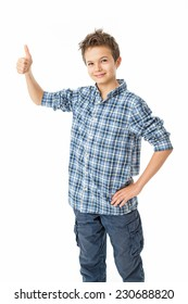 Happy charming Teenage Boy with brown hair, isolated against white wearing a blue white shirt giving a thumbs up sign