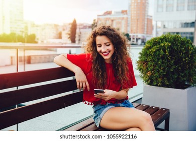 Happy charming young woman with curly hair looking at smartphone screen, typing a message while resting on bench in a city. Dressed in red blouse and jeans shorts.