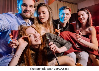 happy cheerful adults, women and men spending day-off in karaoke bar, young ladies and guys wearing party clothes, dresses. energetic and emotional group of people have fun