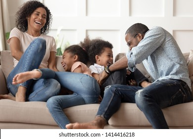 Happy cheerful african american family with cute little kids tickle laugh sit on sofa together, smiling young black parents and children having fun play at home enjoy funny lifestyle activity cuddle