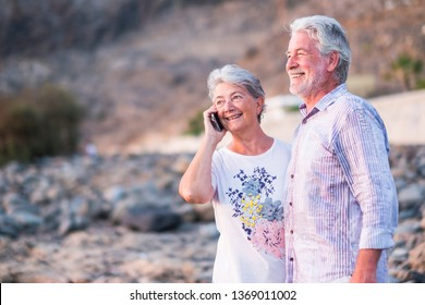 Happy cheerful aged old caucasian couple enjoy and have fun together in outdoor - together forever life concept for beautiful man and woman retired