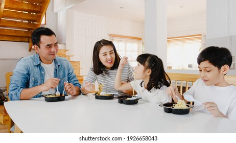 Happy cheerful Asian family having lunch eat spaghetti pasta in plastic container in dining room at modern home. Spending time together, Self-isolation, Social distancing, Quarantine for corona virus.