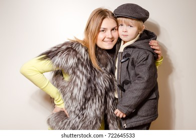 Happy cheerful attractive family kids wearing coats ready for winter season lifestyle. Close up portrait of joyful hugging people with healthy smile on light background