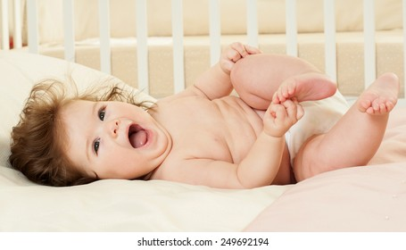Happy cheerful baby in the interior of the bedroom. Laughter.