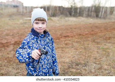 Happy and cheerful baby playing with a gun.