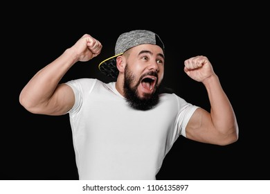 happy cheerful bearded football fan in cap celebrating. emotional man screaming on pink background