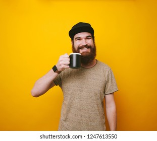 Happy and cheerful bearded hipster man drinking tea or coffee over yellow background