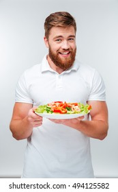 Happy cheerful bearded man holding plate with vegetables isolated on white background