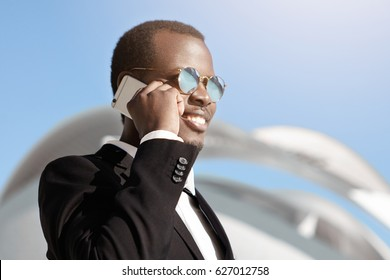 Happy cheerful black businessman in formal wear and sunglasses talking on smart phone outside office builing early in the morning, making appointment for business meeting with potential partners