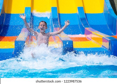 Happy cheerful boy splashing water on water slide at aqua park