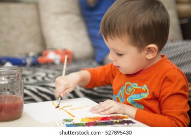 Happy cheerful child drawing with brush using a painting tools. Creativity concept. kids, children painting in kindergarten. kids, children painting in kindergarten. children painting in kindergarten