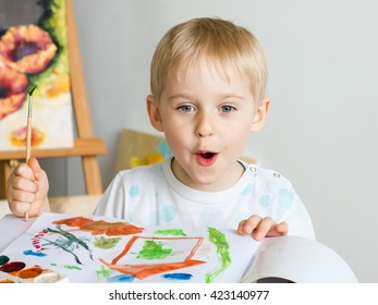 Happy cheerful child draws paints in an album, using a variety of drawing tools. Creativity concept boy holding a brush, a happy childhood