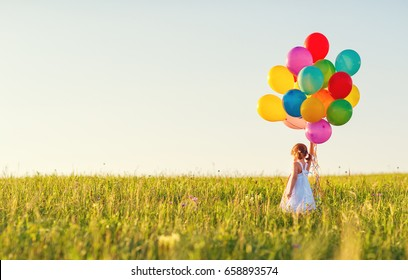 Happy cheerful child girl with balloons on meadow at sunset on nature in summer