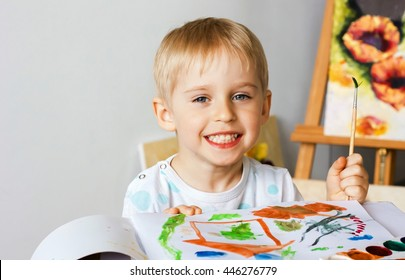 Happy cheerful child paint with   album using a lot of tools for drawing. Creativity concept boy draws paints and holds a brush, a happy childhood, soft focus