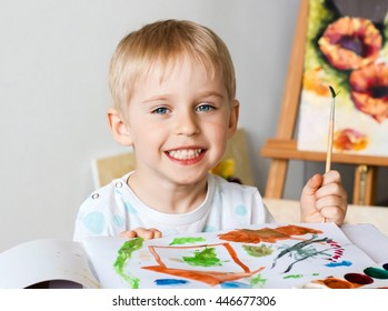 Happy cheerful child paint with brush in album using a lot of tools for drawing. Creativity concept boy draws paints and holds a brush, a happy childhood, soft focus