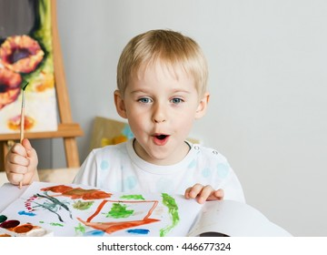 Happy cheerful child paint with brush in album using a lot of tools for drawing. Creativity concept boy draws paints and holds a brush, a happy childhood   Selective focus