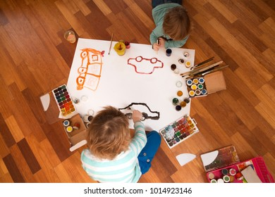 Happy cheerful children drawing with brush in paper using a lot of painting tools.   Top view.