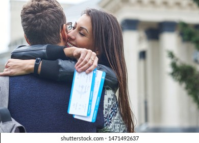 happy cheerful couple hugging and showing flying tickets. man making a surprise to a woman - giving tickets for a honeymoon.