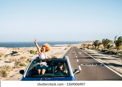 Happy cheerful couple of young caucasian crazy woman with curly hair enjoy the travel and vacation staying outside the roof of a convertible car with long road and ocean in background - happiness joy
