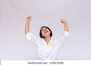 Happy and cheerful cute Asian business teenage woman raising hands up for success and celebration in white isolated background